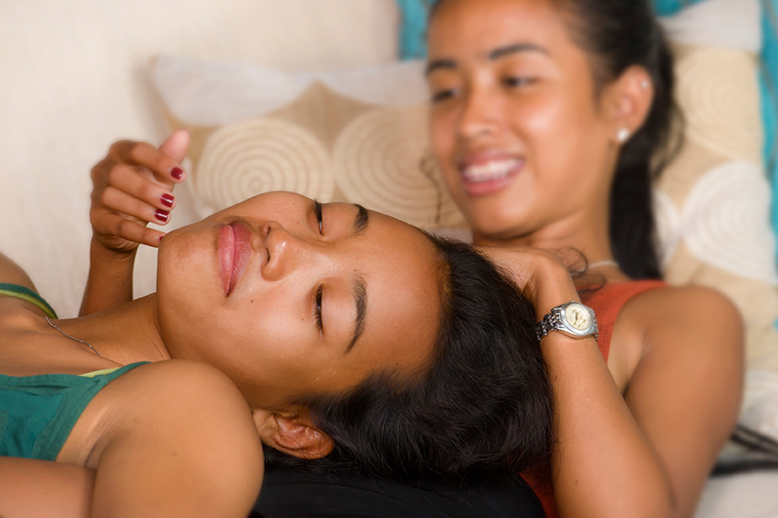 Happy Beautiful Asian Girlfriends Laughing and Cheerful Together Having Fun At Home on the Sofa Couch Cuddling