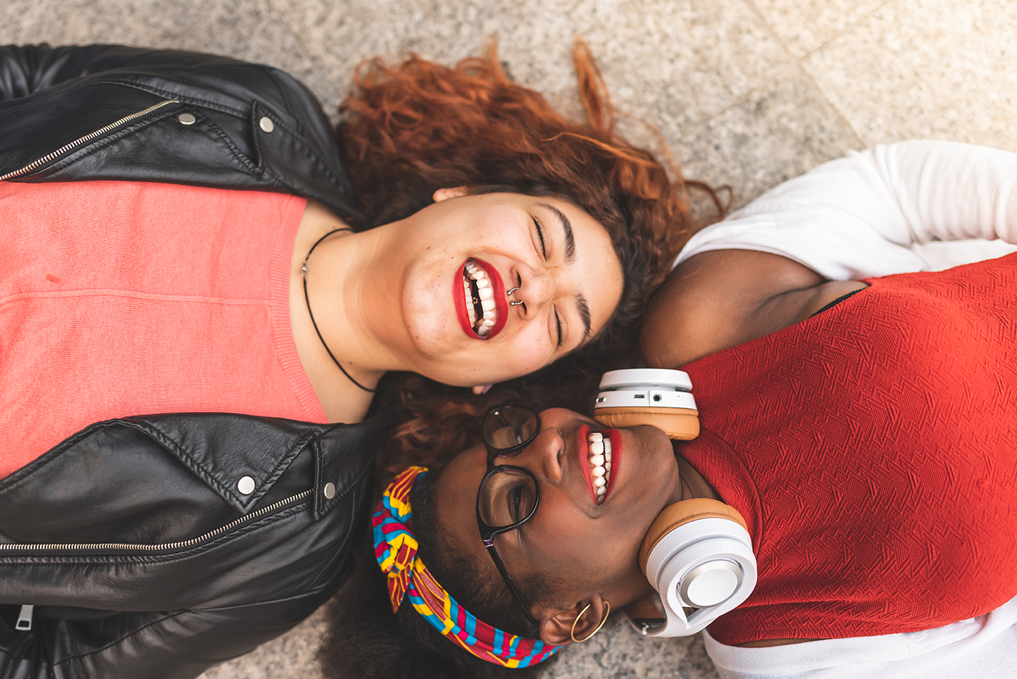Two Teenage Girls Laying Down ; Looking Each Other and Smiling.