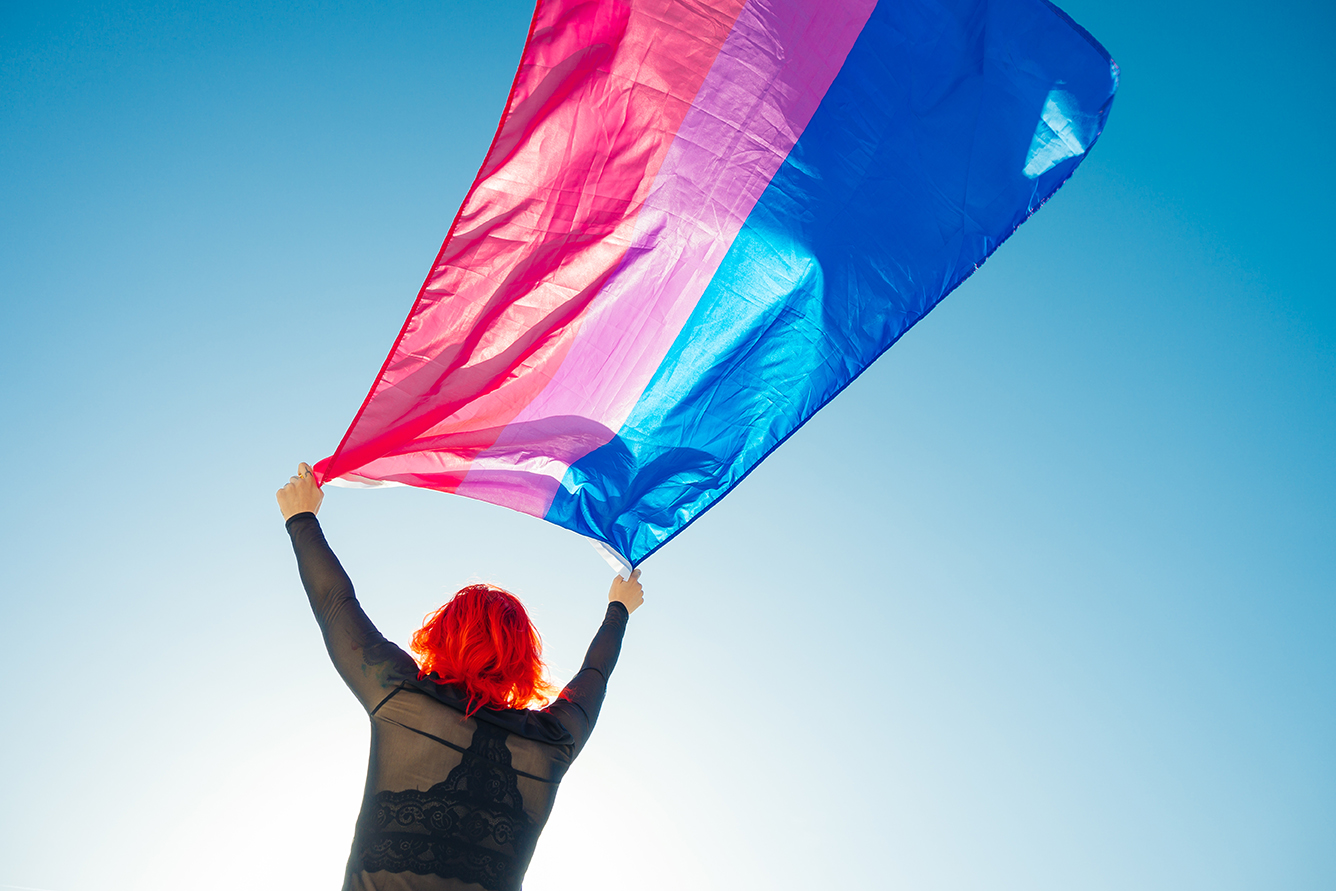 Person holding the Bisexual Rainbow Flag with the blue sky in the background