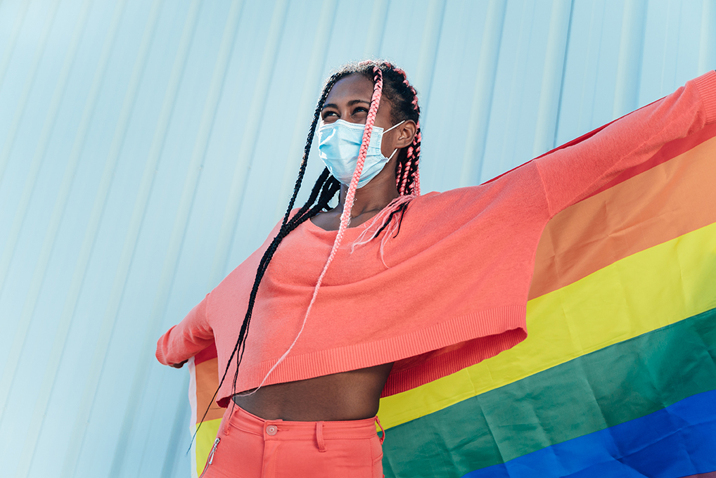 Young black gay woman with face mask holding a lgbt gay pride rainbow flag