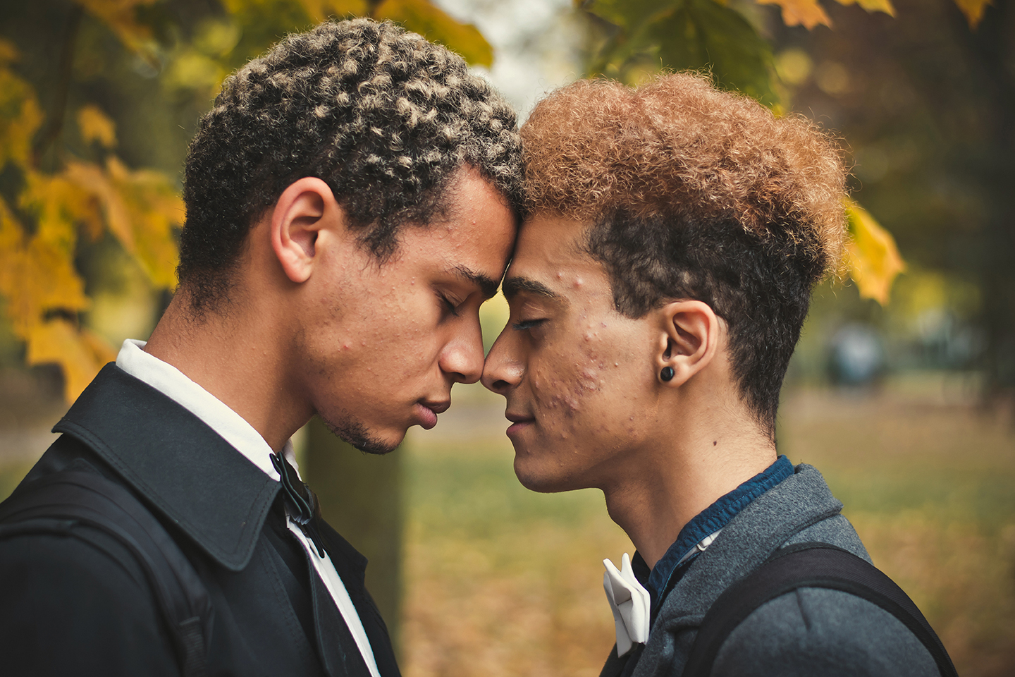 Handsome young gay couple standing head to head in park.